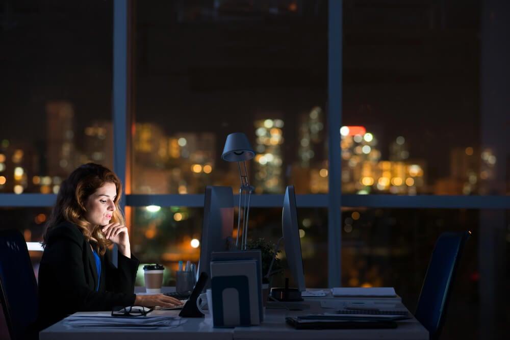 mulher profissional trabalhando sozinha em escritório a noite