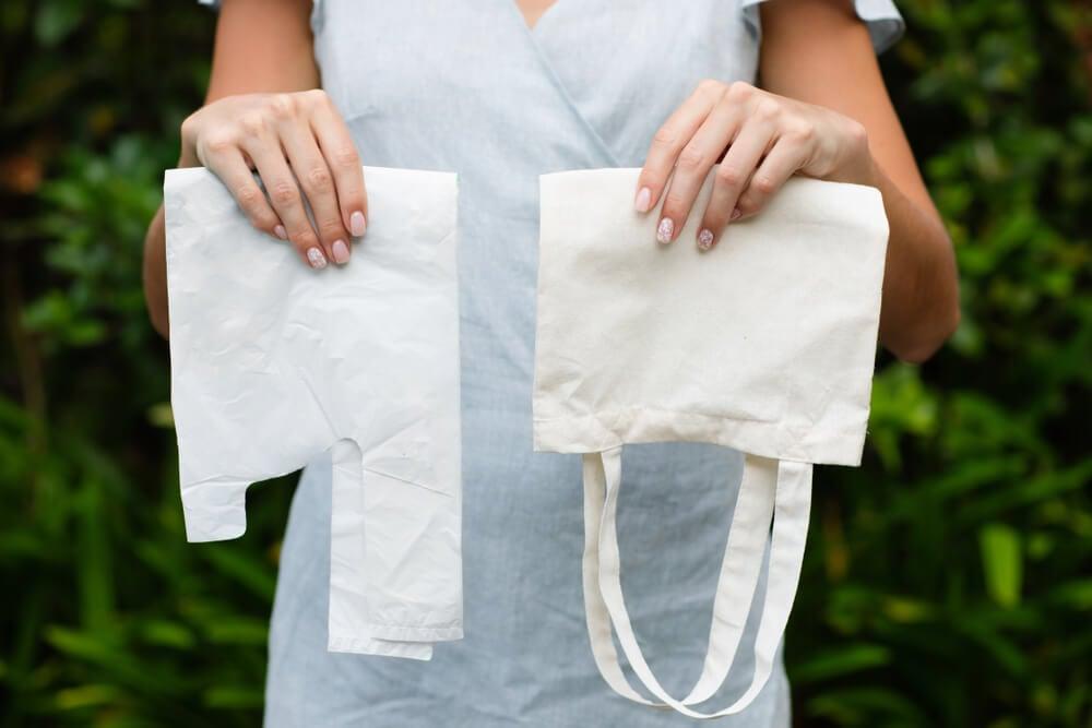 mulher segurando sacolas de pano e plástico induzindo consumo consciente