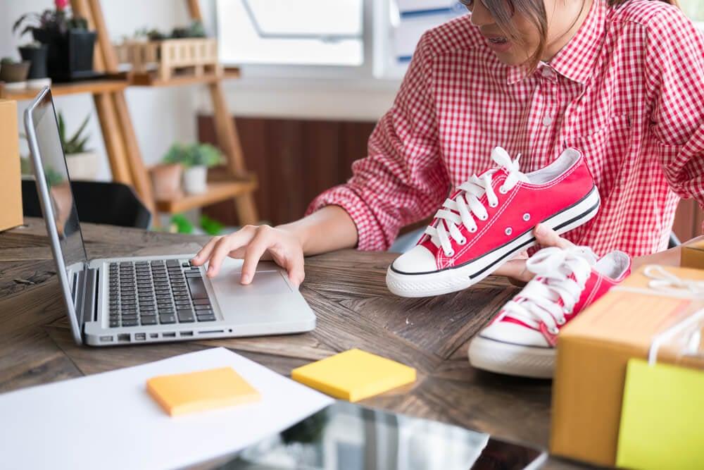 mulher segurando sapato de encomenda vinda de clube de assinatura em frente a computador