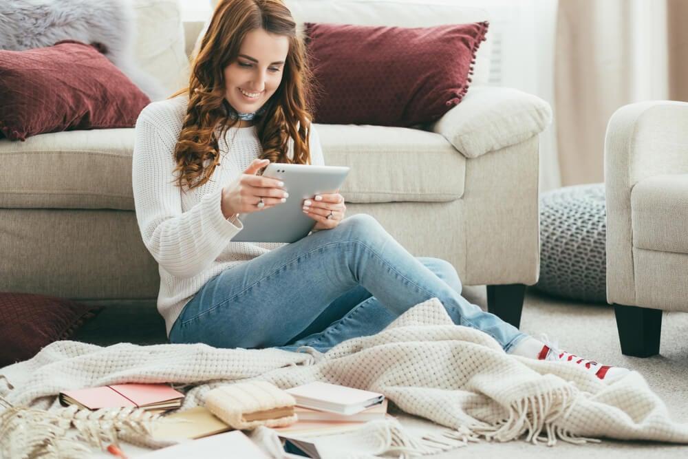 mulher sorridente acessando tablet em sala de estar
