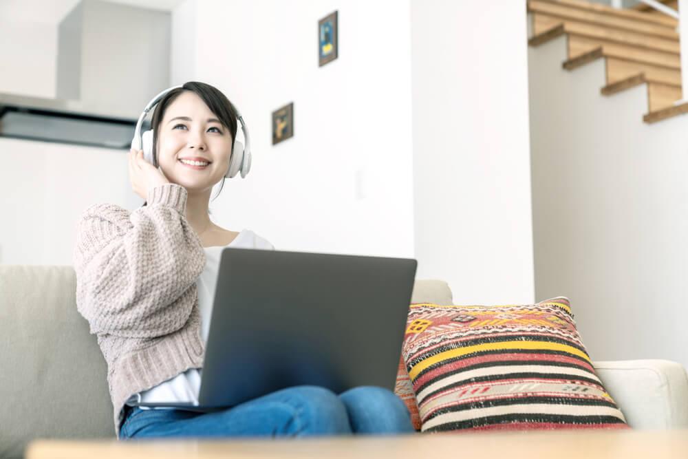 mulher sorridente em frente a laptop e fones de ouvido