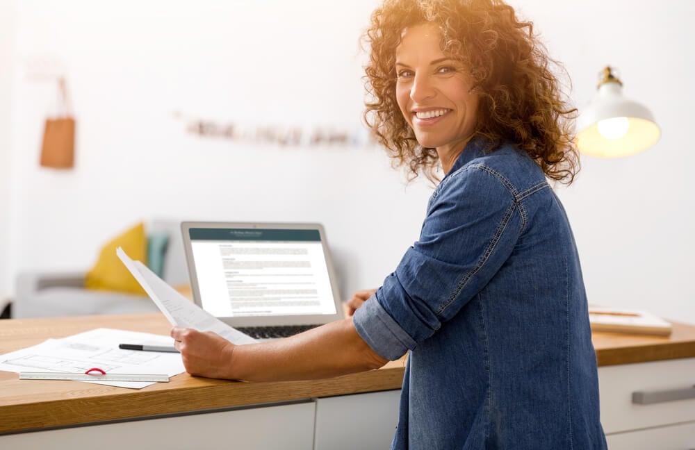 mulher sorridente em frente a laptop