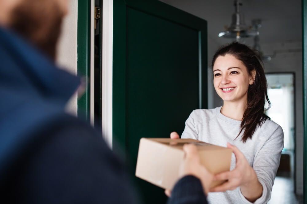 mulher sorrindo ao receber caixa de clube de assinatura na porta de sua casa