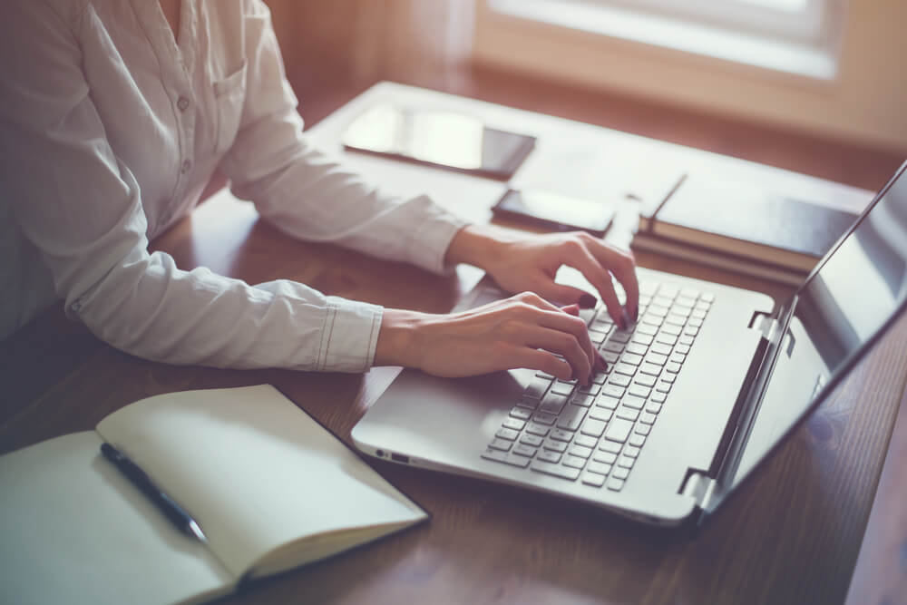 mulher teclando em laptop em mesa executiva com bloco de notas ao lado