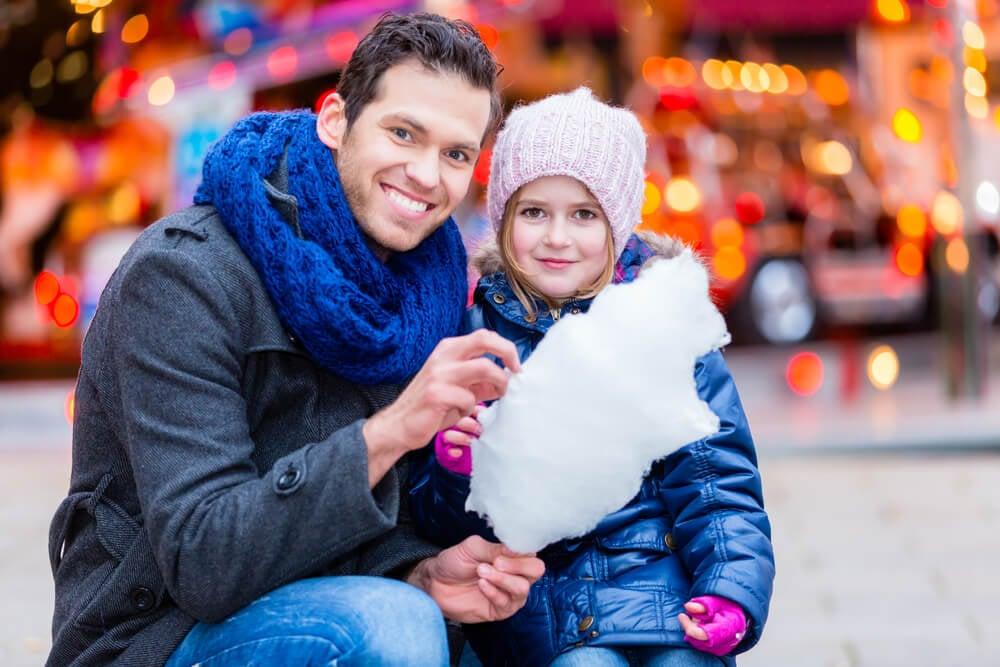 pai e filha consumindo algodão doce em centro de publicidade infantil