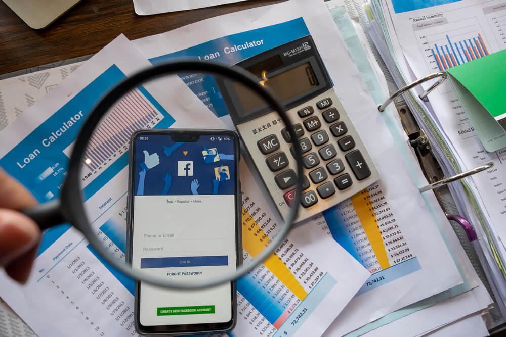 papéis com gráficos e calculadora acompanhando smartphone acessando o aplicativo mobile facebook