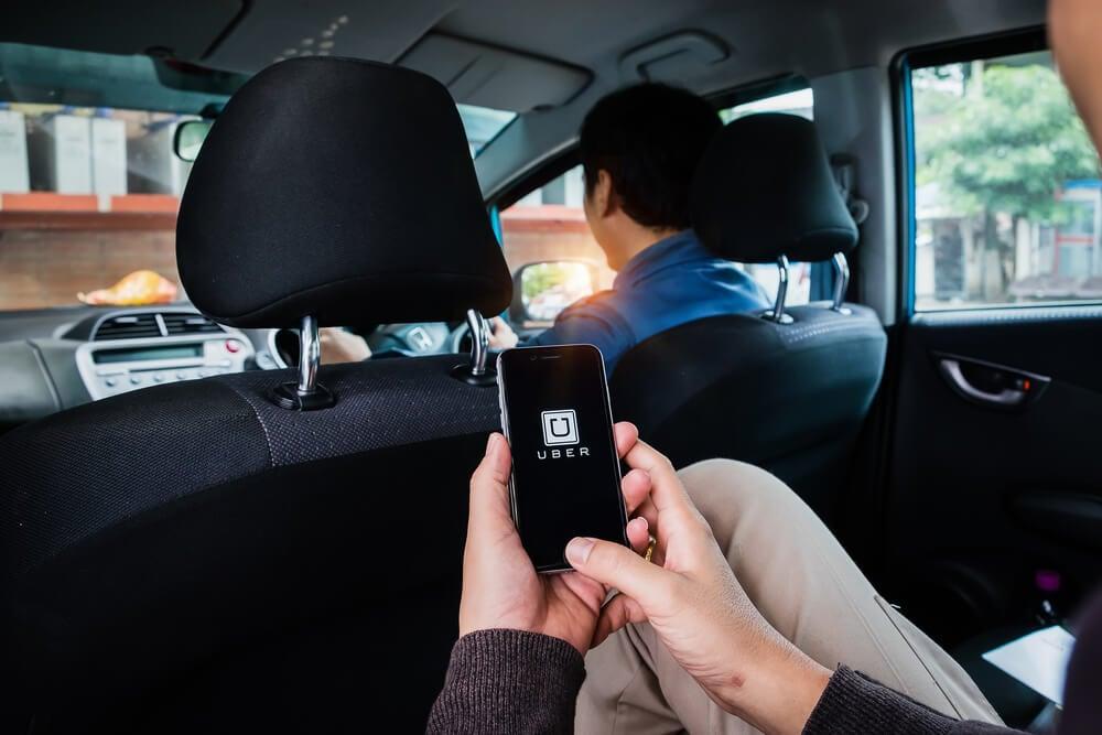 passageiro em carro com smartphone em maos no aplicativo uber
