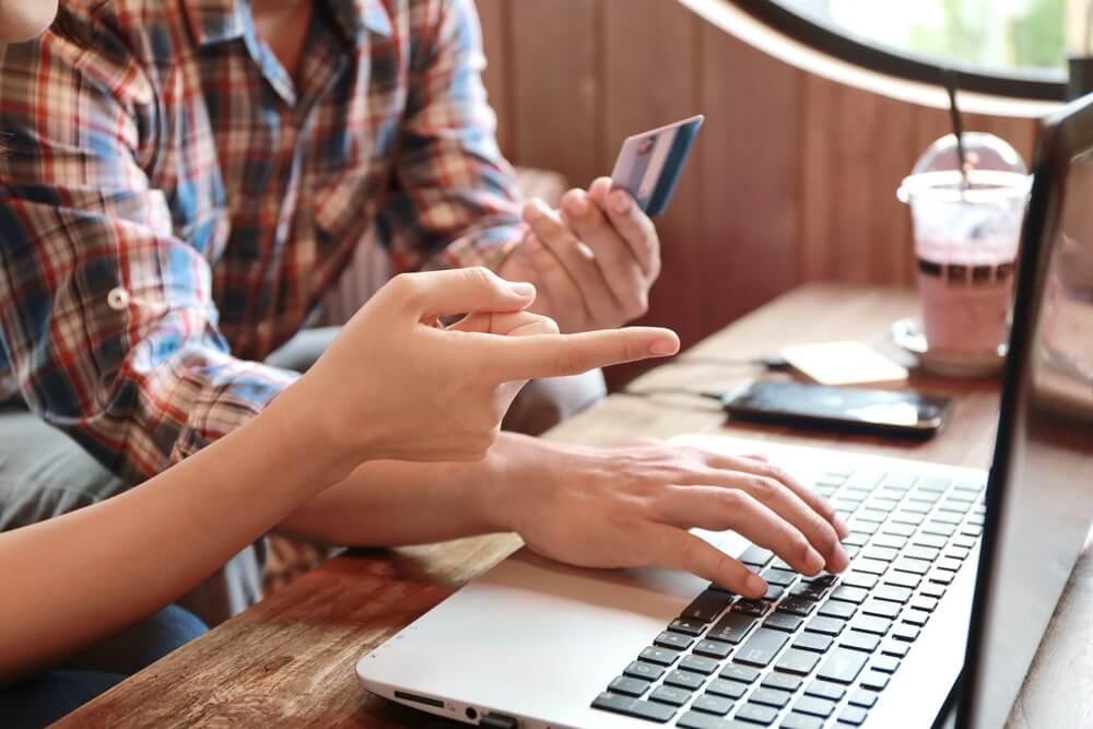 pessoas acessando laptop segurando cartão de crédito