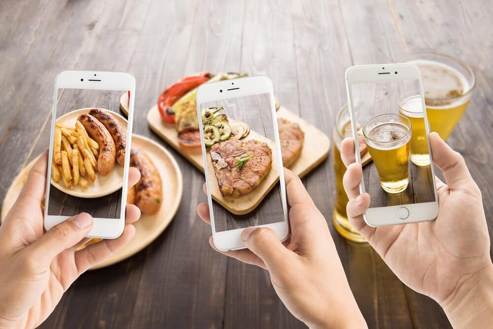 pessoas tirando fotos de comidas e bebidas com smartphones