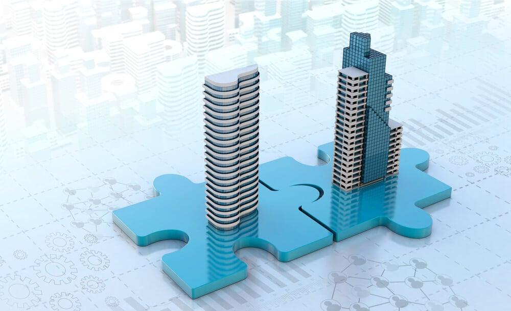 prédios sobre peças de quebra cabeça representando fusão de companhias