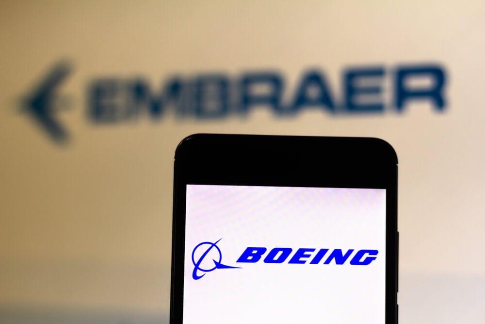 primeiro plano comk logo da empresa boeing em smartphone e fundo com logo da empresa Embraer