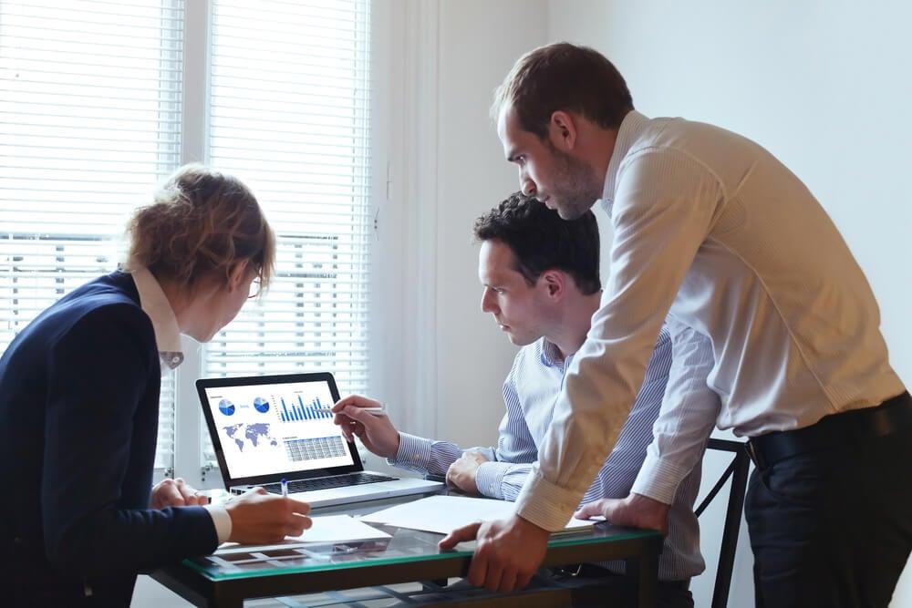 profissionais em relaçoes publicas em torno de laptop discutindo negocios