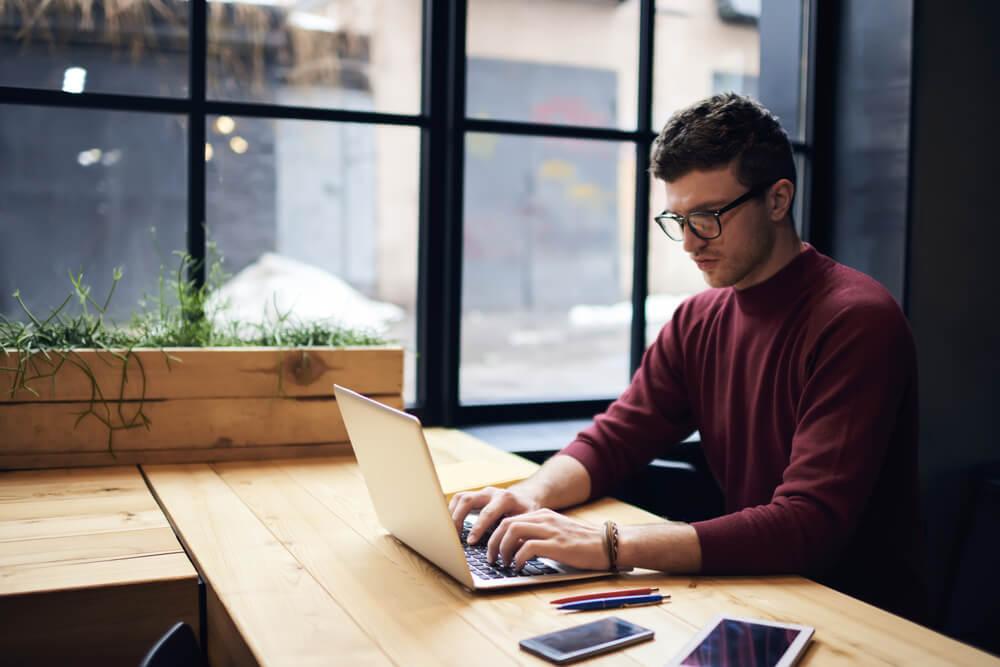 profissional de copywriter trabalahndo em laptop concentrado
