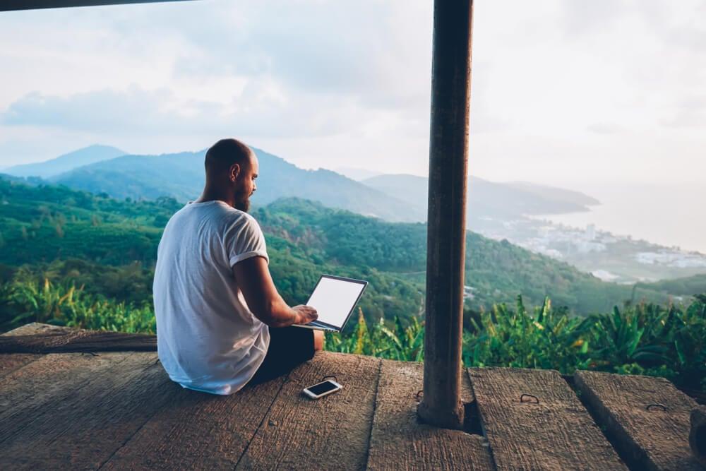 profissional de trabalho remoto sentado em sacada com paisagem de fundo