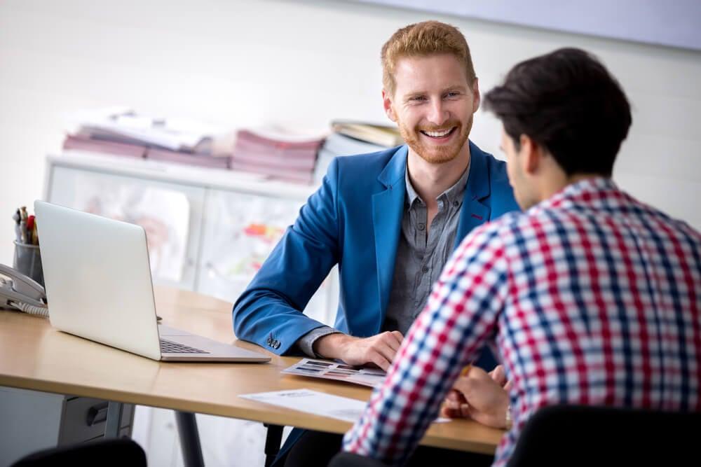 profissional de vendas atendendo cliente sorridente em mesa