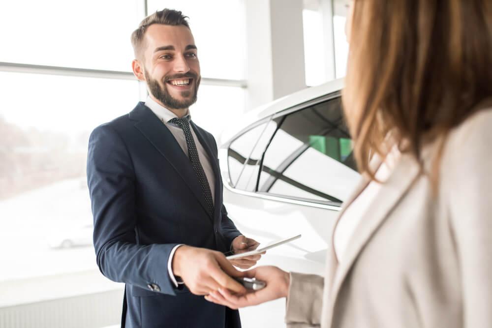 profissional em venda de automoveis exercendo sua profissao ao entregar chaves para cliente