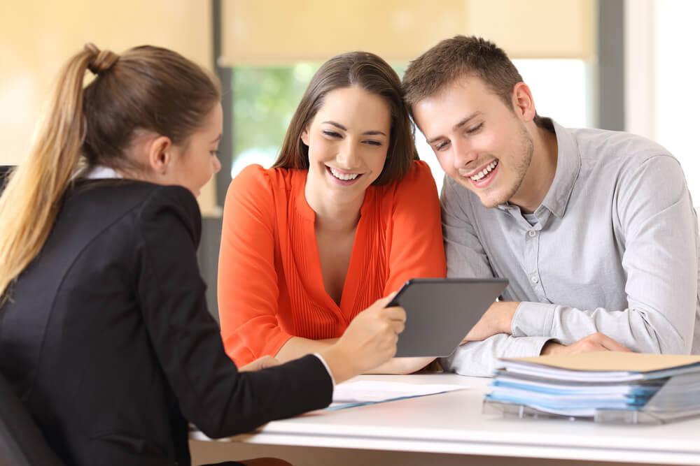 profissional em vendas em conversaçao com clientes ao mostrar tela de tablet