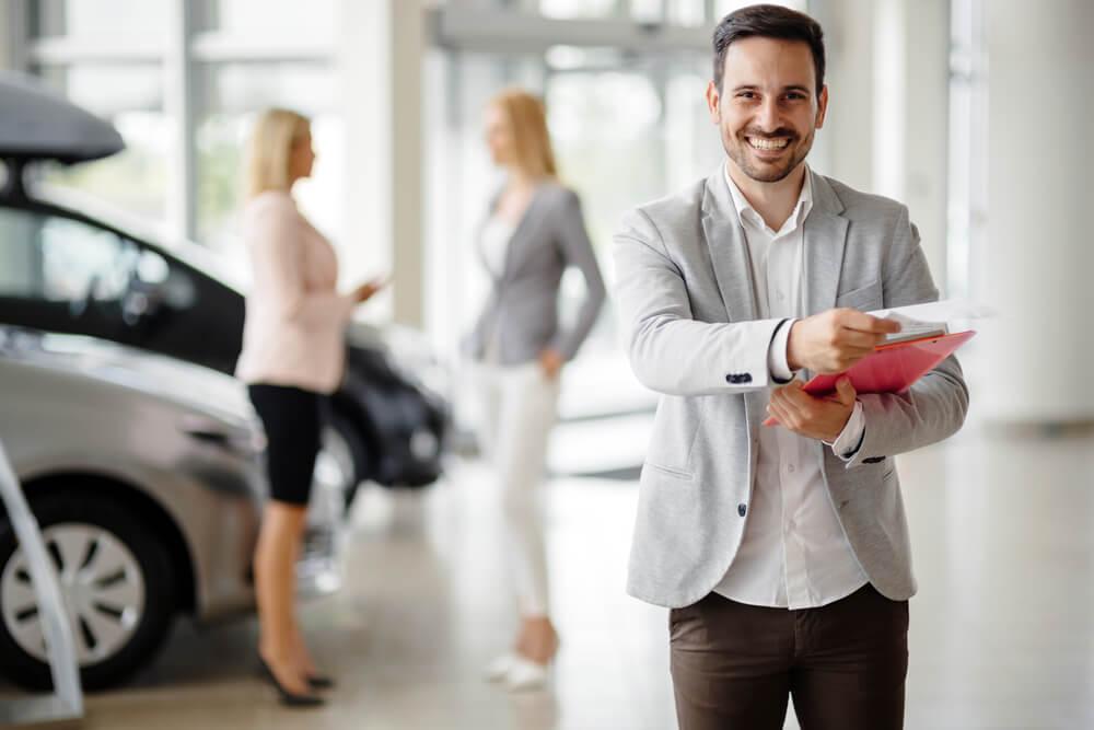 profissional gerente de vendas sorridente em loja de carros