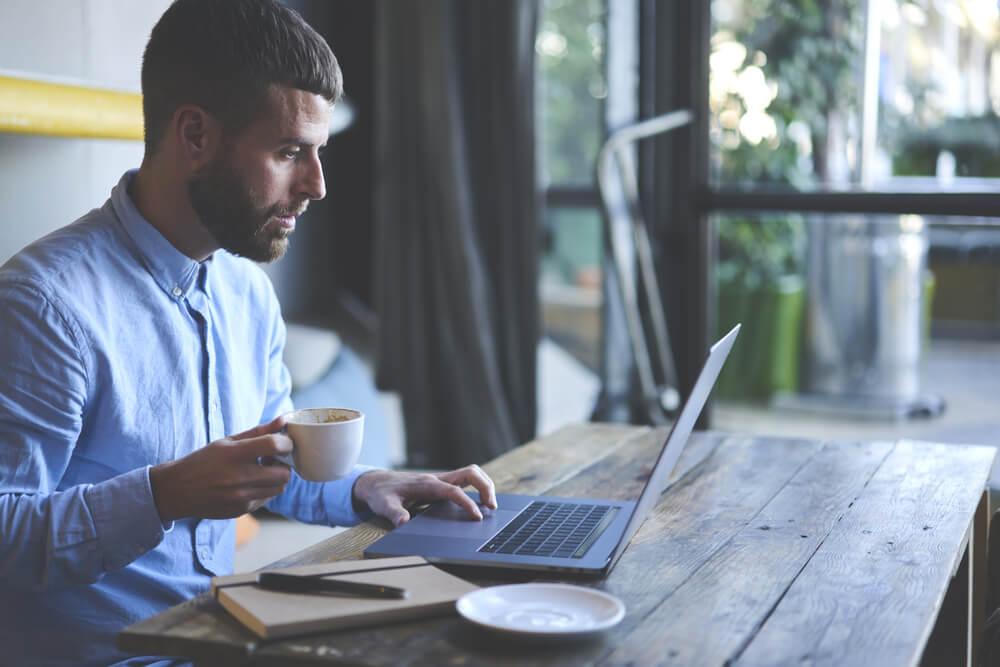profissional trabalhando em cafeteria com laptop