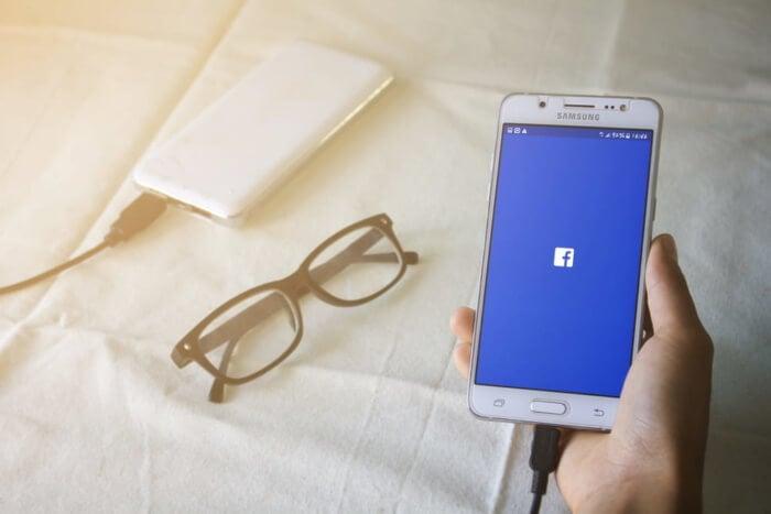 smartphone acessando facebook junto de óculos