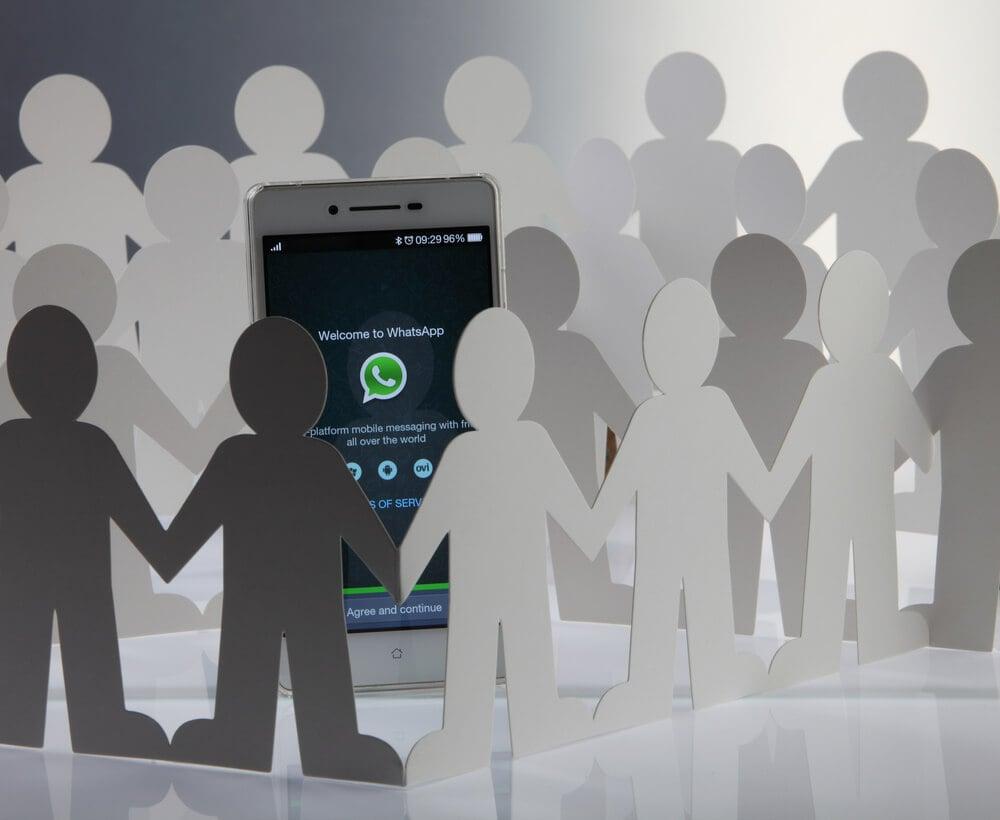 smartphone com icone do aplicativo whatsapp e ilustraçao de bonecos de papel ao redor simbolizando grupos de whatsapp