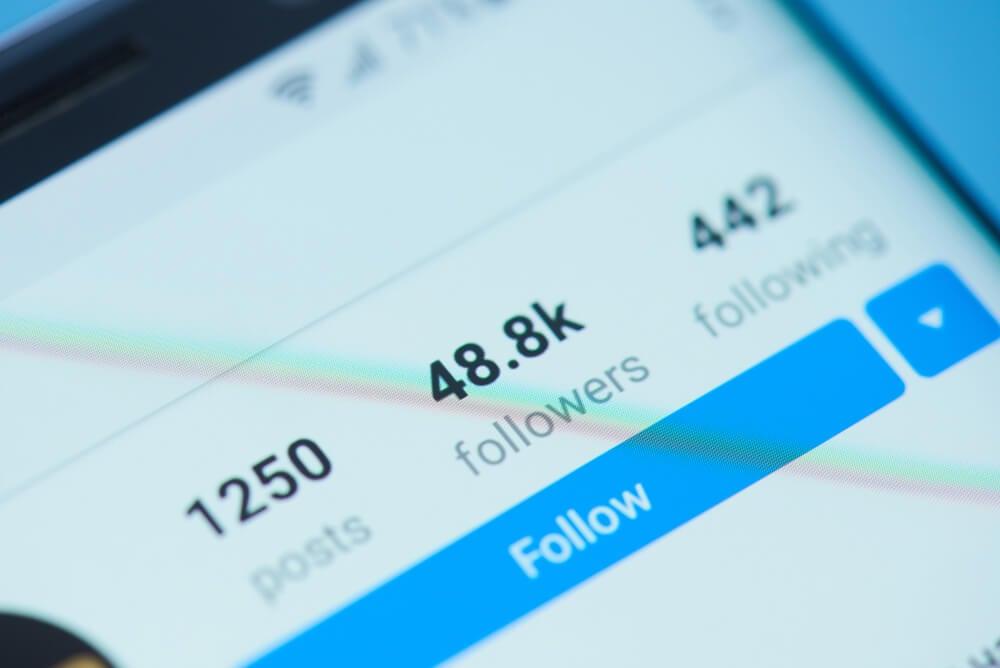 smartphone com perfil do aplicativo instagram mostrando seguidores seguindo e postagens em tela