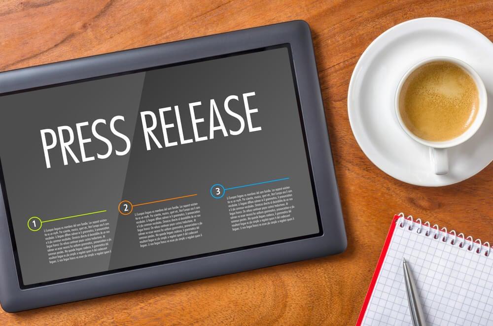 tablet com passos do processo de press release junto de caderno de anotação e xícara de café
