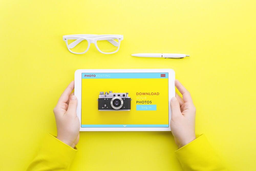 tela amarela com mãos segurando tablet com conteúdos