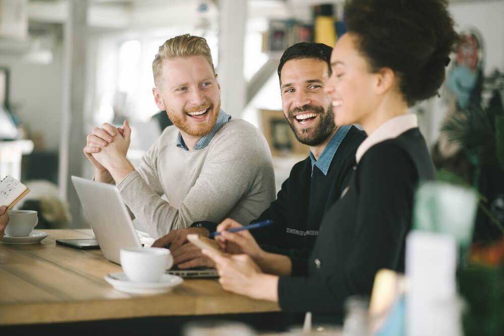 trio de colegas de trabalho sorridentes em mesa de café