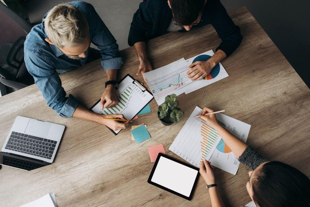 visão de cima de mesa com equipe de administração de marketing e papéis com gráficos