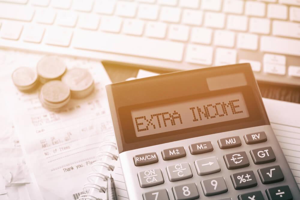 calculadora em mesa com computador com título renda extra
