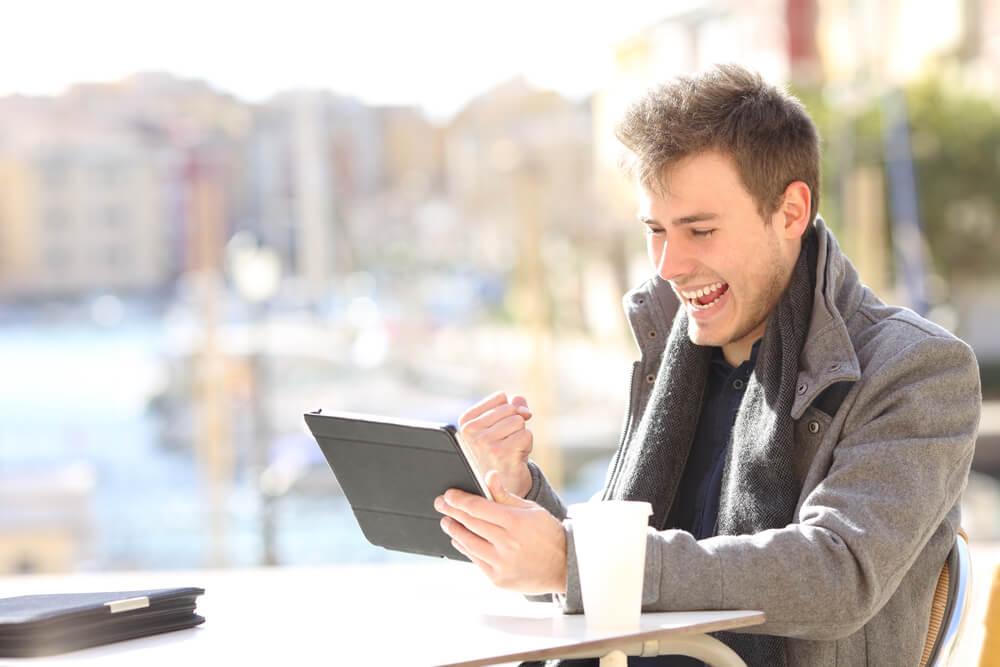 cliente acessando tablet e com expressão de comemoração