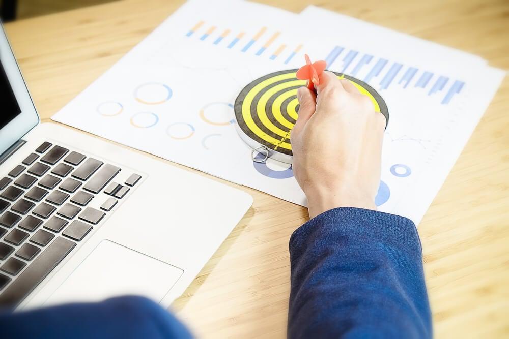 dardo em alvo em mesa com laptop e métricas de marketing