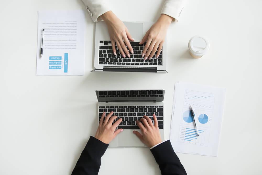 dois laptops em mesa com profissionais trabalhando nos mesmos simbolizando parcerias de negocios