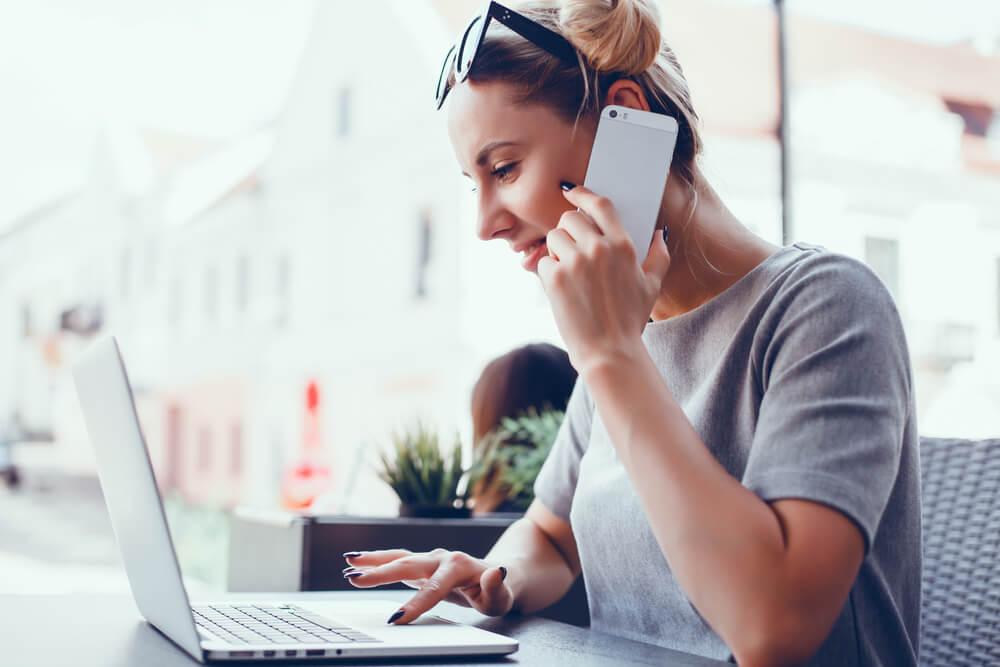 garota ao telefone e acessando laptop