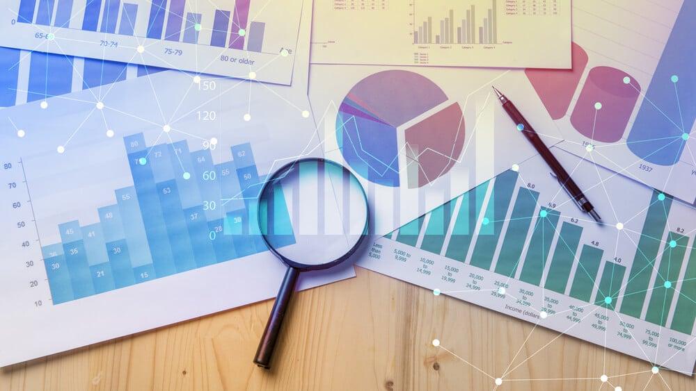 gráficos de estudo de mercado junto de lupa em mesa
