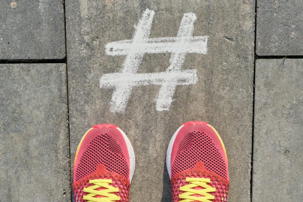 hashtag pintada no chão junto de tênis de corridoa para contas no instagram sobre saúde e fitness