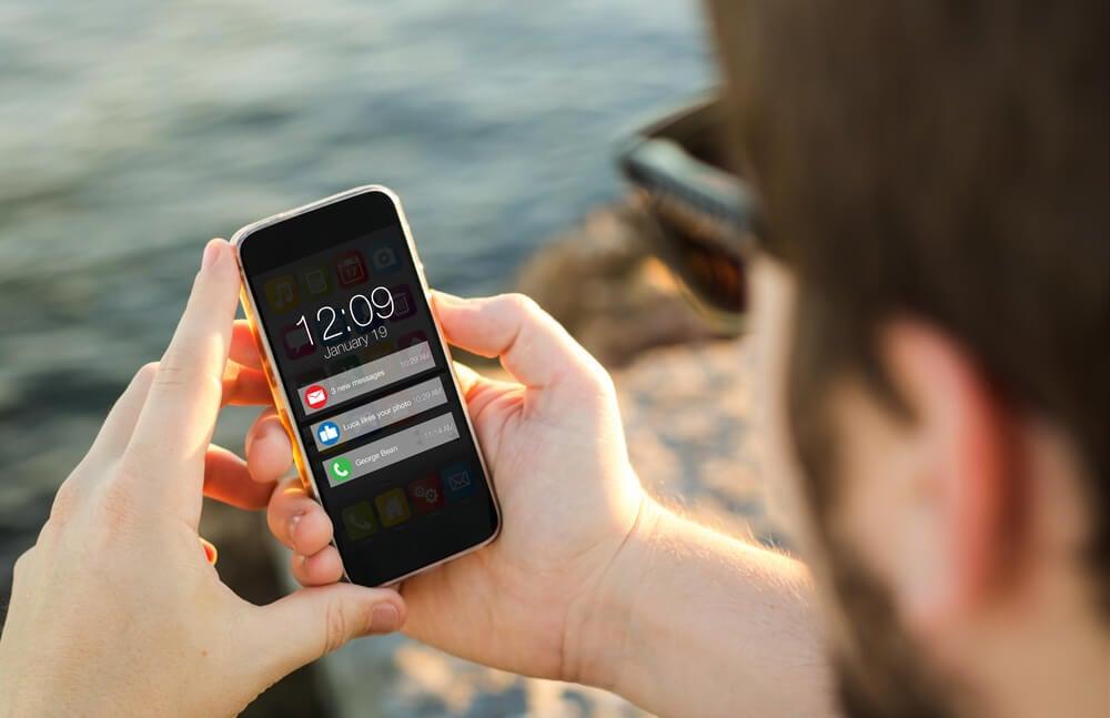 homem com smartphone em maos mostrando notificaçoes push em tela