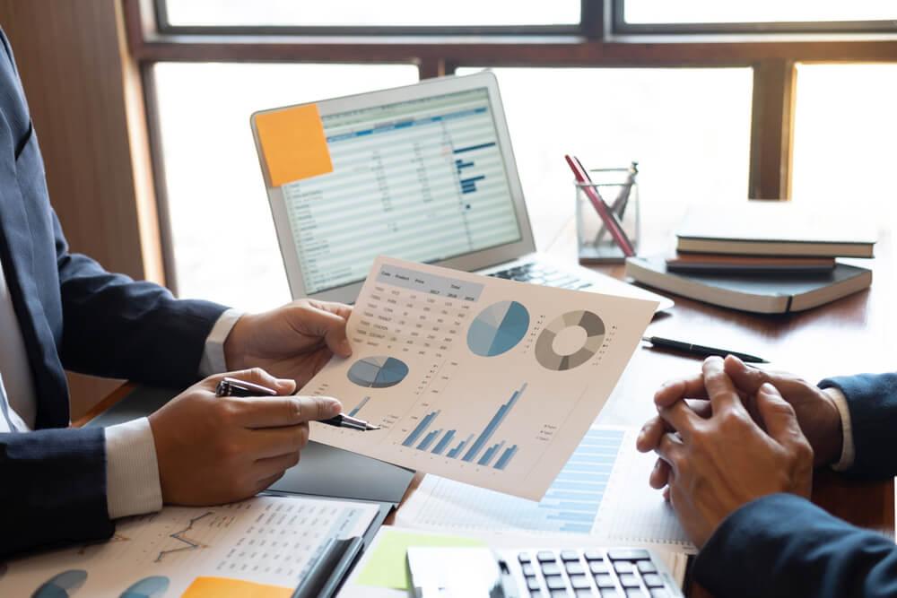 homem de terno indicando com caneta graficos em papel em frente a computador em mesa com materiais de escritorio