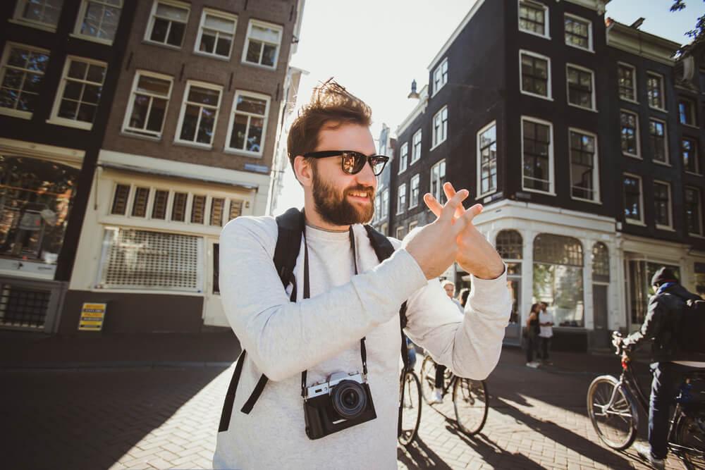 homem fotógrafo fazendo símbolo de hashtag com as mãos