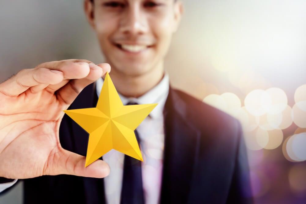 homem segurando estrela representando satisfação e qualidade
