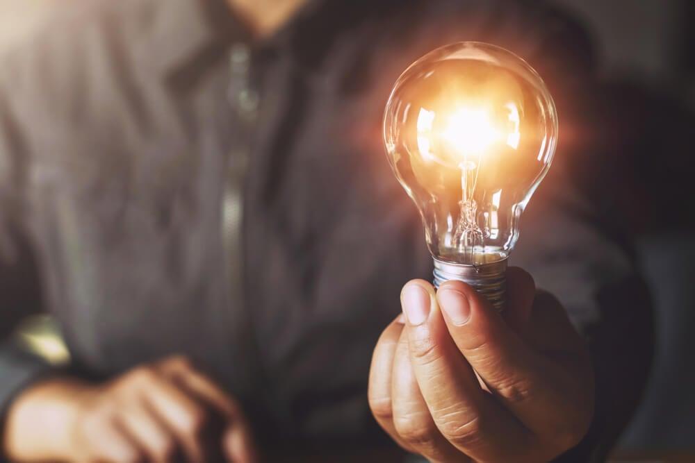 homem segurando lampada acesa simbolizando ideias