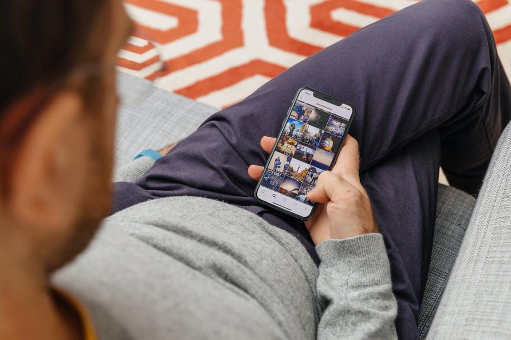 homem sentado de pernas cruzadas com smartphone em maos em feed de aplicativo instagram