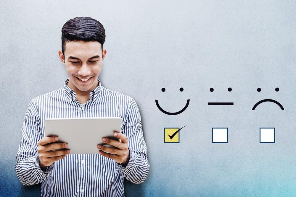 homem sorrindo ao olhar para tablet em suas maos e feedback positivo ao lado