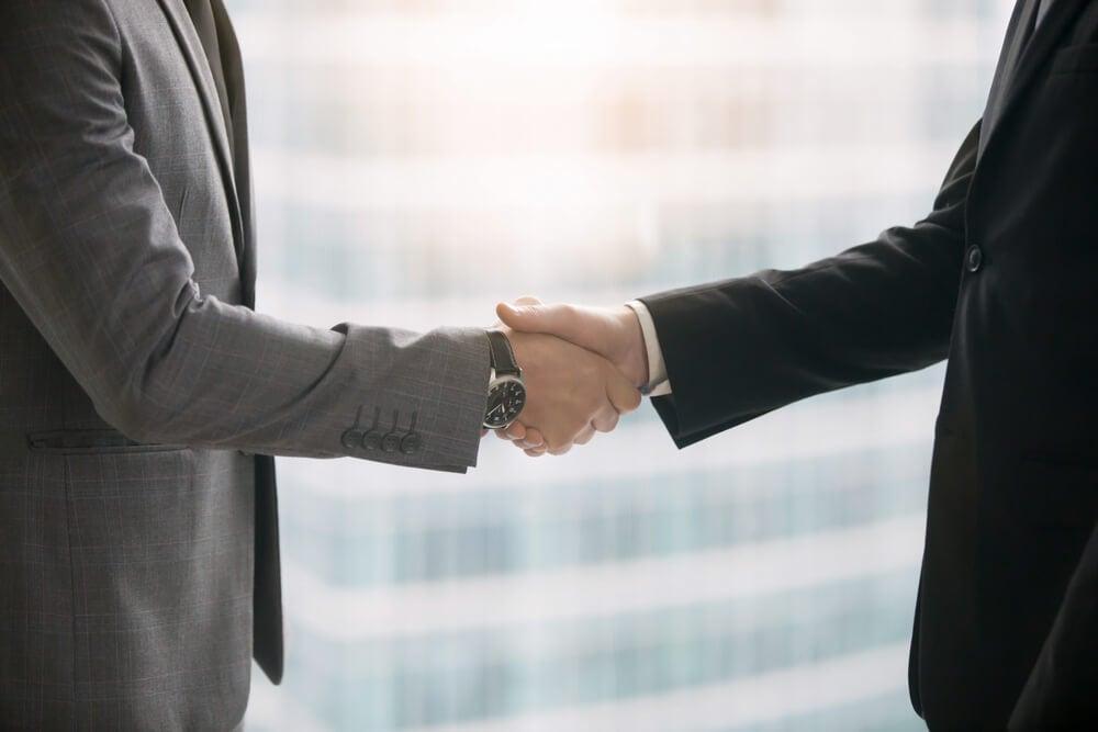 homens executivos fechando negocios ao apertarem maos