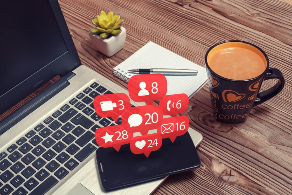laptop com smartphone sob e ilustração de notificações