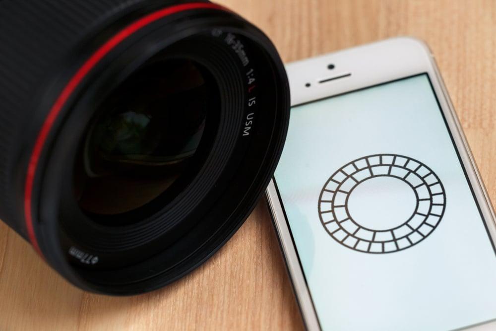 lente de camera ao lado de smartphone com icone de aplicativo VSCO cam em tela