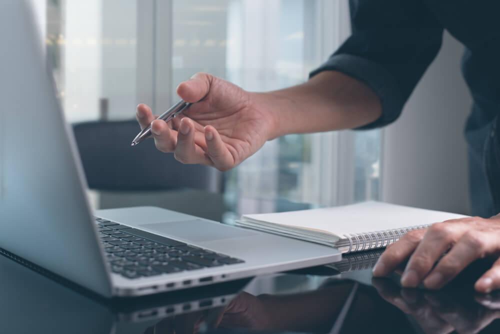 mão assinalando laptop em processo de criação