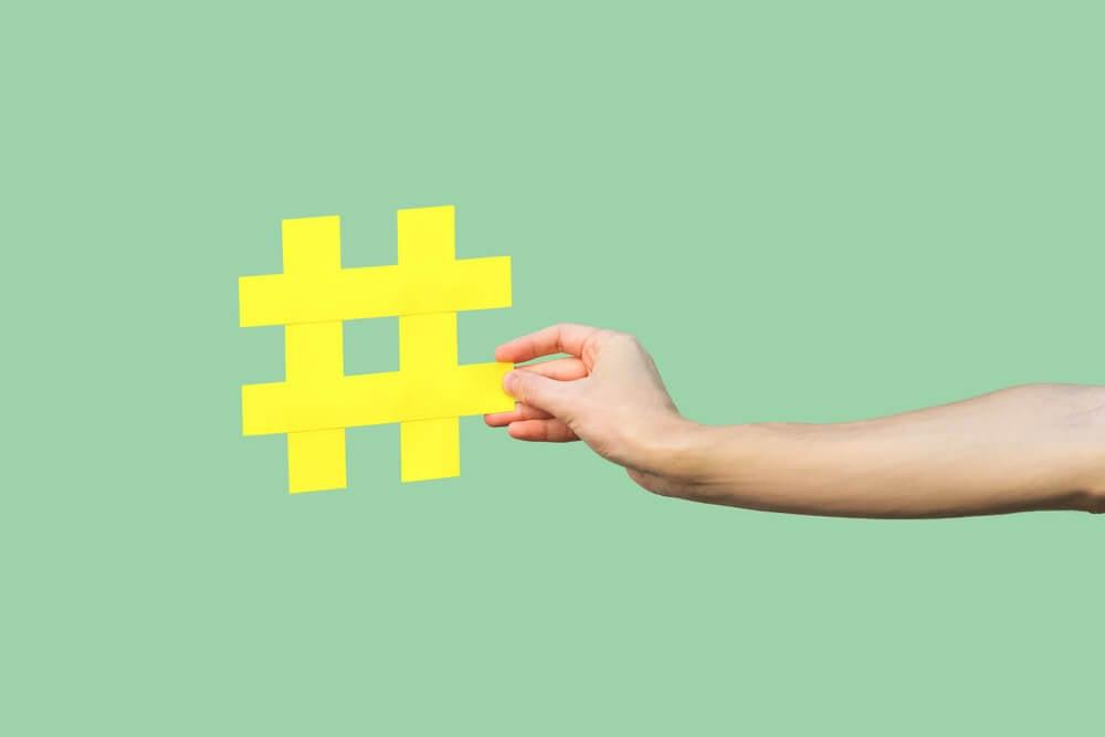 mão feminina segurando hashtag amarela em fundo verde