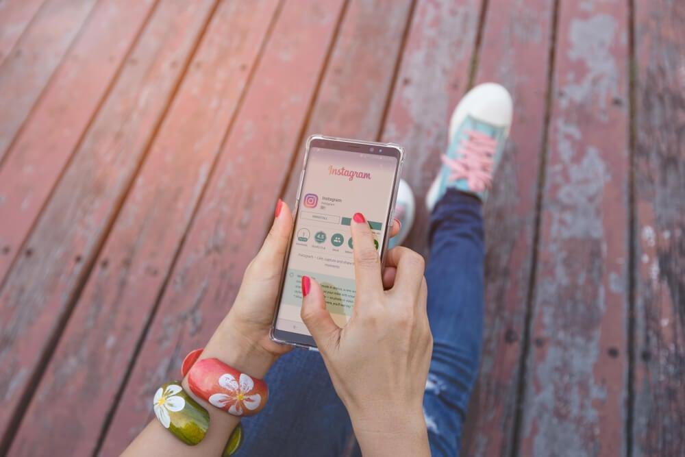 mão feminina segurando smartphone acessando o aplicativo instagram